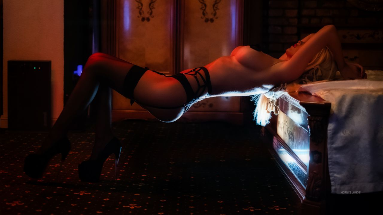 Athletic camgirl about to start a BDSM session in a dark room with red lights
